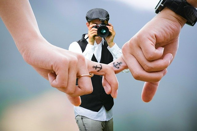 photographer taking a picture of two people linking fingers with anchor tattoos