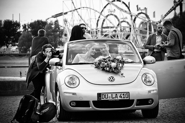 wedding photographer taking picture of couple just married in car