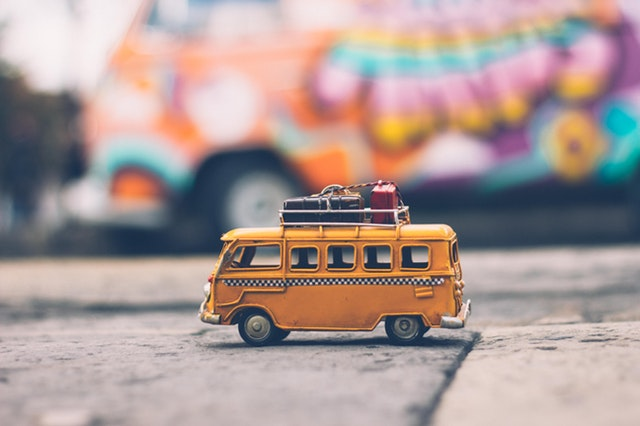 yellow toy bus with luggage on top