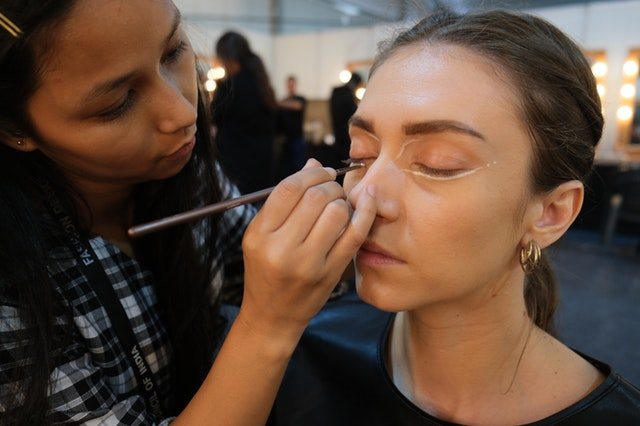 woman doing eye makeup to another woman