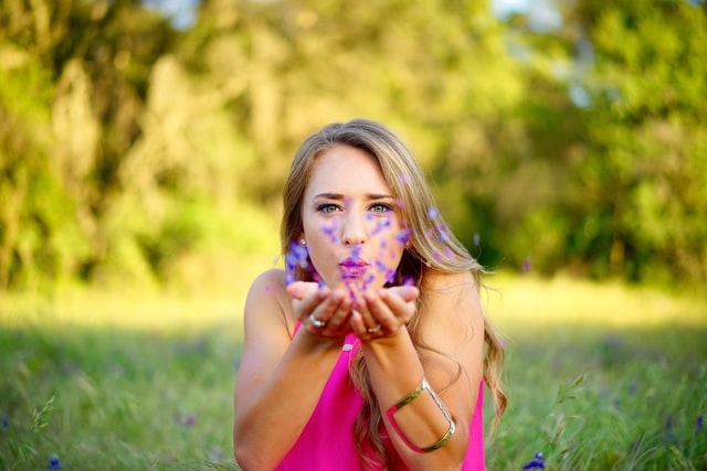 Girl blowing petals of flowers