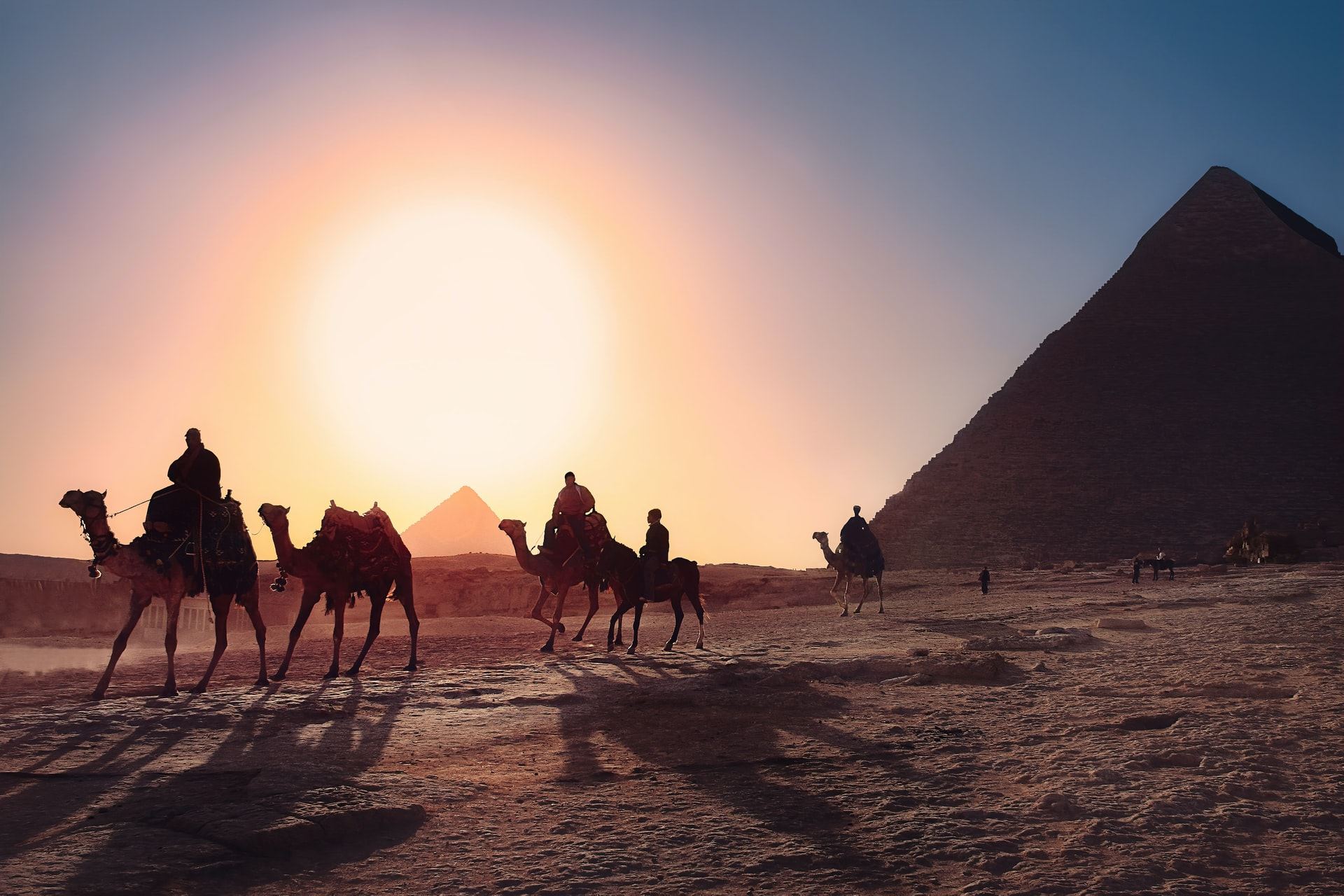 people riding camels in Egyptian desert near pyramids