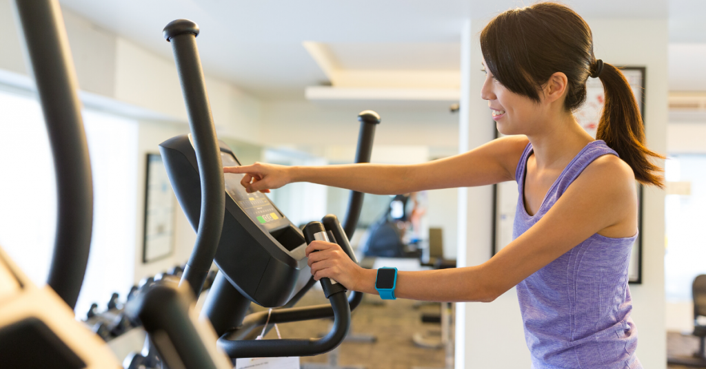 Woman training on elliptical machine in the gym