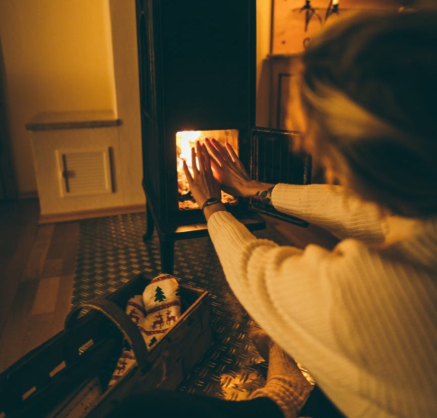 person in sweater sitting by fireplace