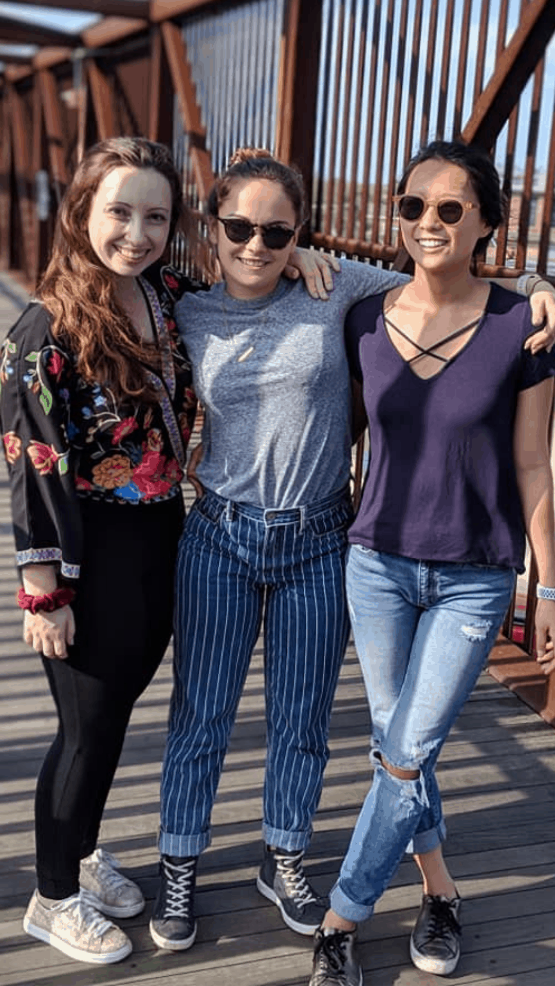 three women standing on a bridge getting good relationship advice