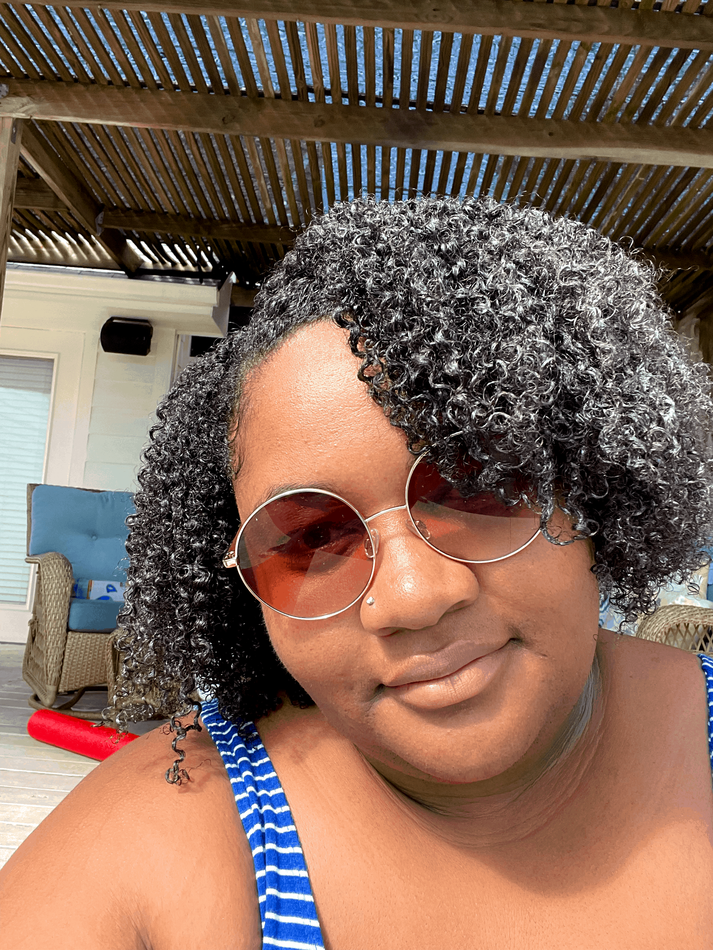 black woman with natural curly 2c hair smiling