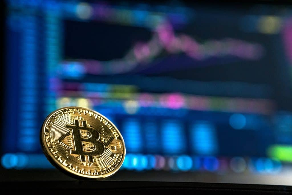 cryptocurrency in foreground with blurred stocks behind