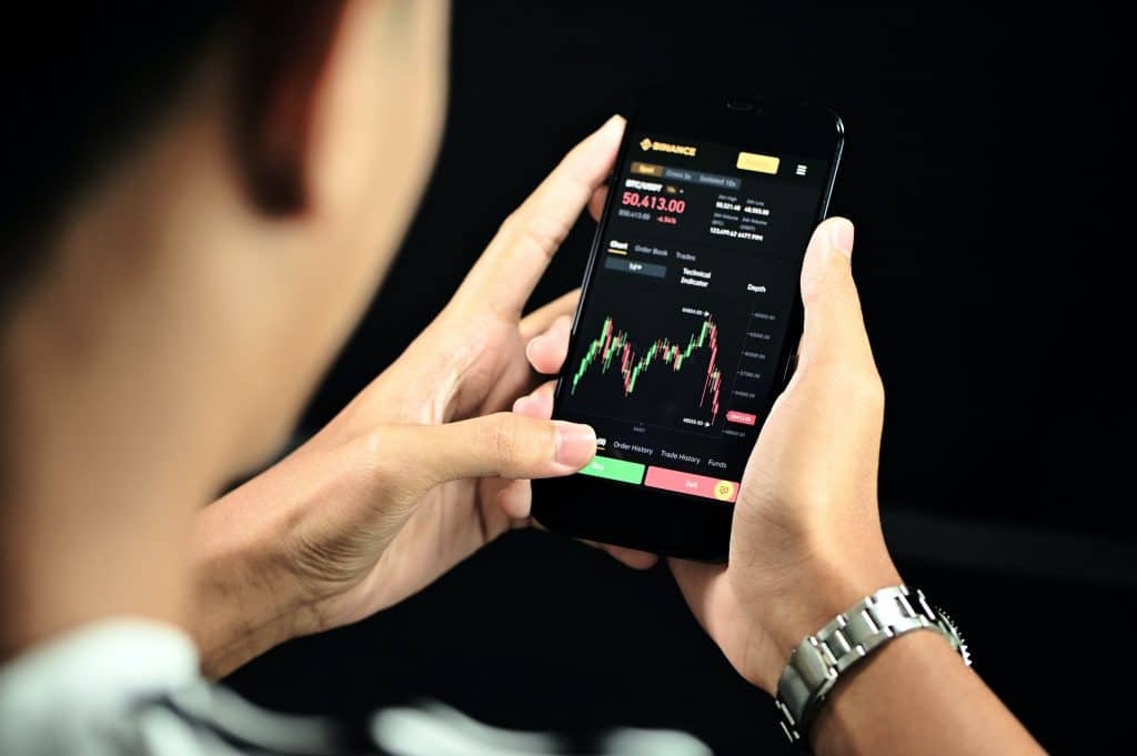 Man looking at cryptocurrency stocks on cell phone