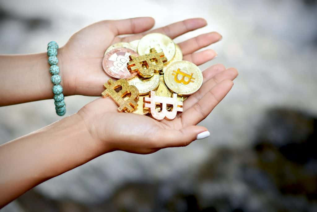 Woman with beaded bracelet holding cryptocurrency