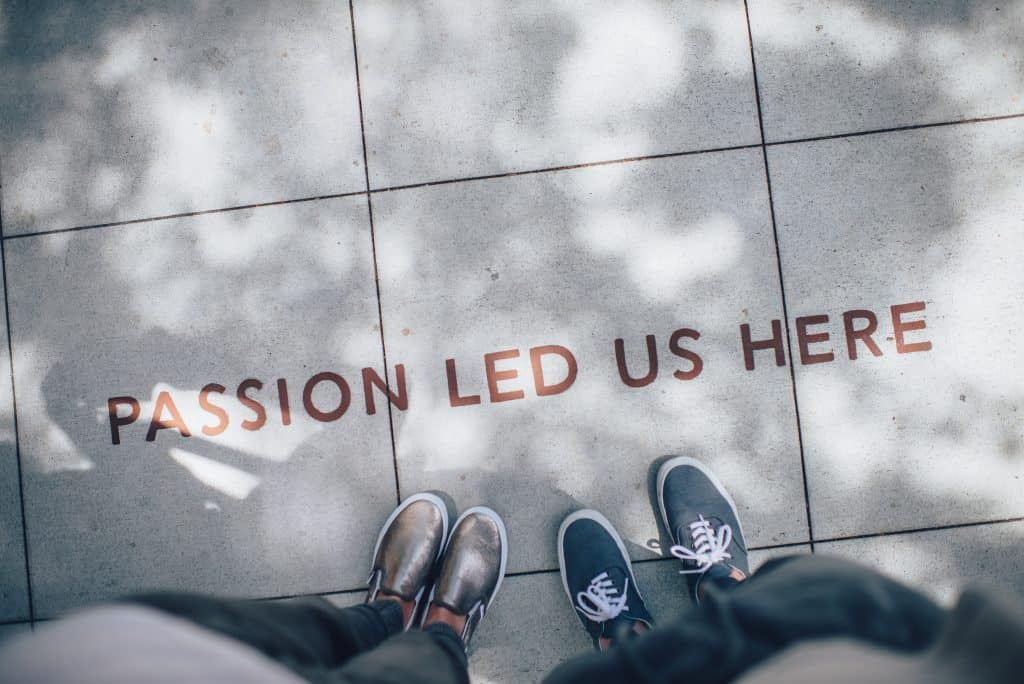 passion led us here written on ground with two pairs of feet