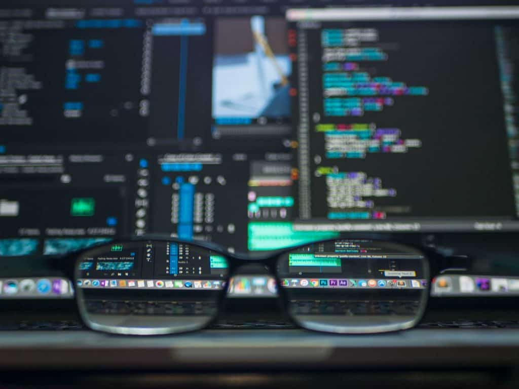 A pair of black glasses in front of a blurred hacker screen
