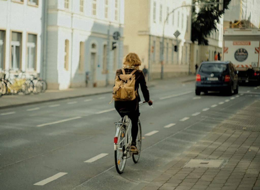 Woman riding a bicycle with a vehicle ahead of her