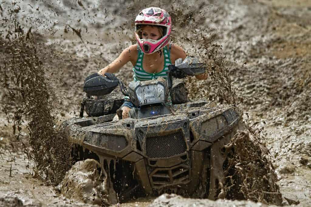 Woman riding a vehicle (ATV) through mud