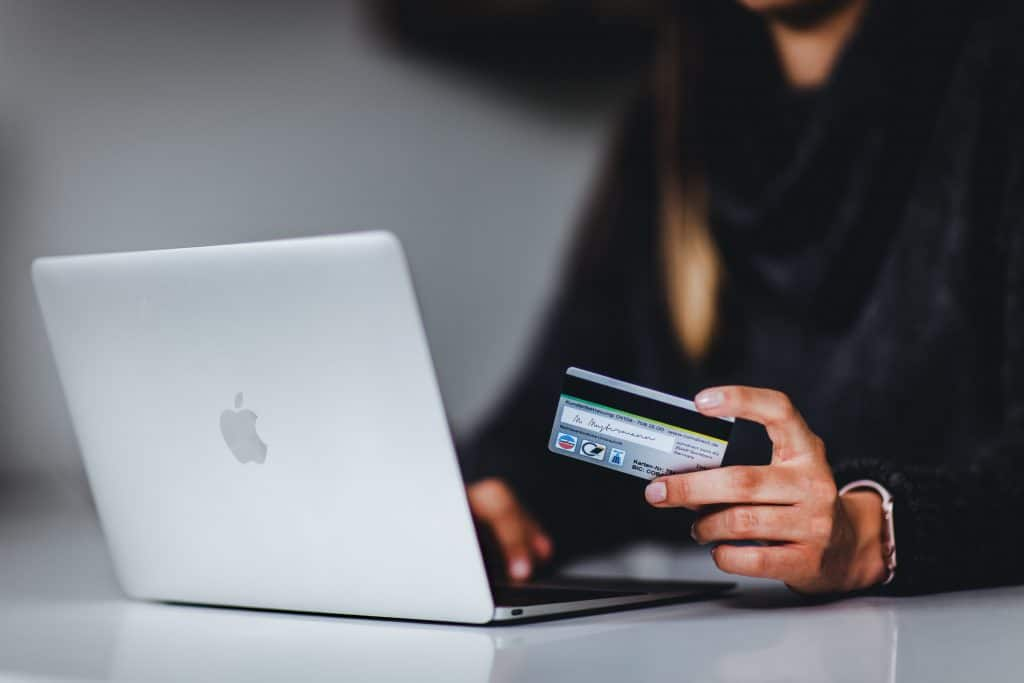 A person shopping at an online store with credit card in hand