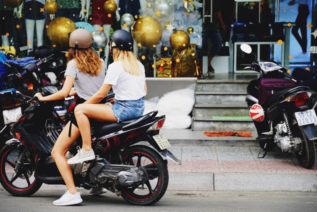 Two women on a vehicle (motorcycle)
