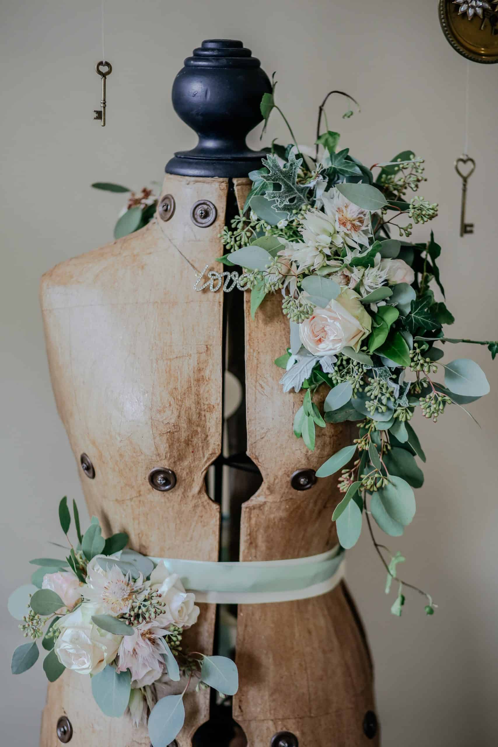 Artificial flowers decorating a wooden mannequin.